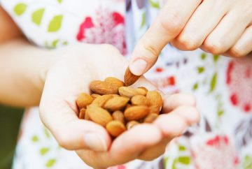 Picture of a woman holding a handful of almonds.