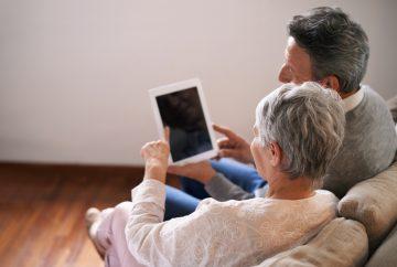 A man and a woman look at an ipad