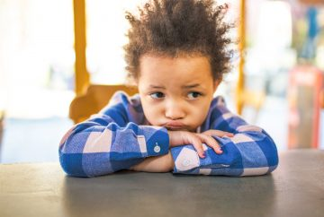 Picture of young child sitting at table looking puzzled