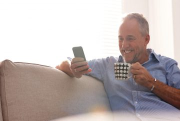 Man smiling holding phone