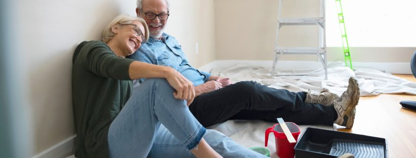 An older couple sitting on the floor of a room they just painted.