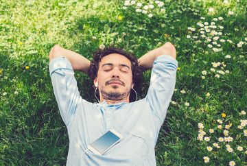 Picture of a man lying in the grass listening to music