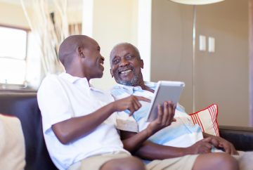 Picture of an older man and a younger man on a couch looking at a tablet screen laughing.