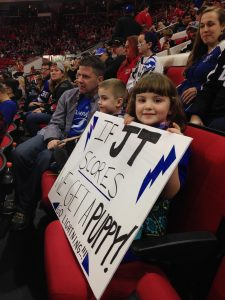 Picture of two kids holding a sign sitting in a hockey arena.