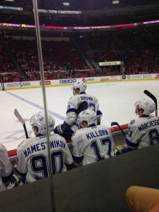 Picture of hockey players on bench and one getting out of the bench.