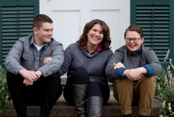 Picture of a woman sitting on her porch with her two sons