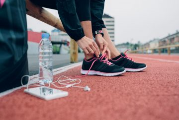 Picture of a woman lacing up her sneakers on a track
