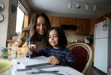 Mother helping child do homework