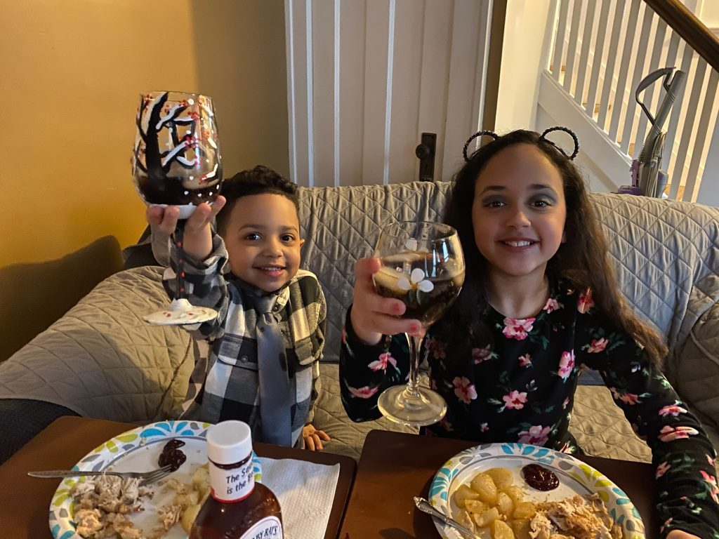 Picture of two children raising a glass to cheers over dinner