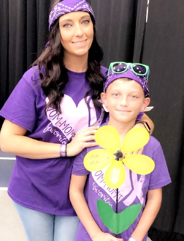 A woman and her son dressed in purple at a community event