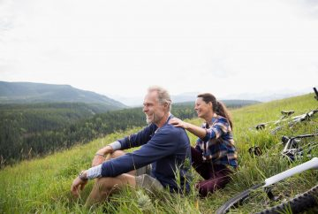 Man and woman sitting on a hill by valley
