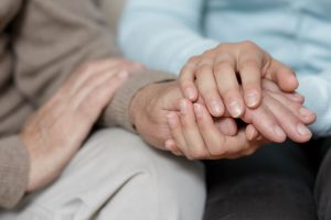 A caregiver holding someone's hands
