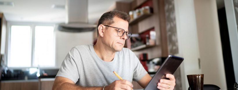 Picture of a man sitting at a table with an ipad