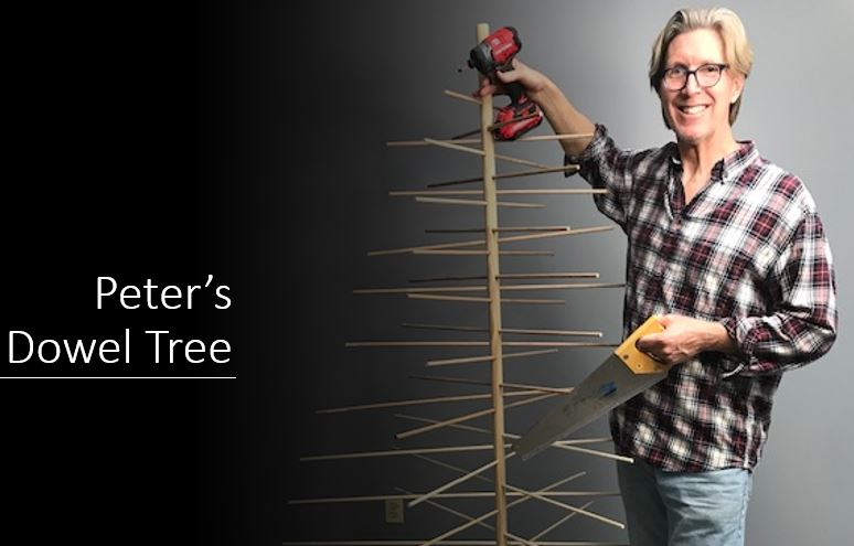 Picture of a man standing next to a tree made of dowels