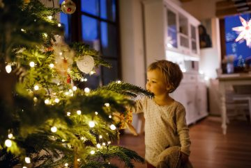 picture of a boy standing next to a christmas tree