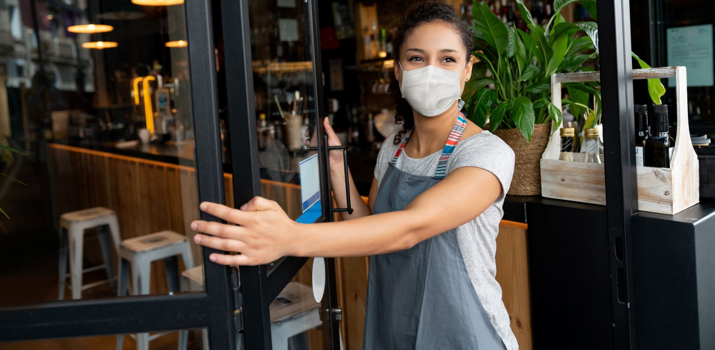 Picture of woman in mask opening door